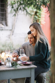 Romantic couple having a candlelight meal at garden table - ALBF00746