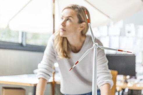 Woman in office working on wind turbine model - TCF06014