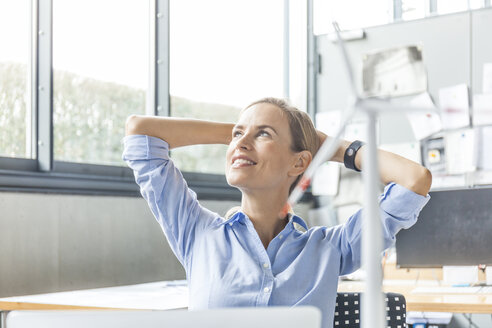 Smiling woman in office with wind turbine model in foreground - TCF06017