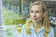 Portrait of woman in office behind windowpane - TCF06038