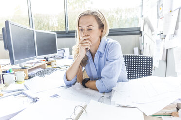 Pensive woman sitting at desk in office surrounded by paperwork - TCF06050