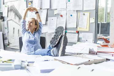 Woman relaxing at desk in office surrounded by paperwork - TCF06053