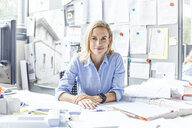 Portrait of confident woman sitting at desk in office surrounded by paperwork - TCF06056