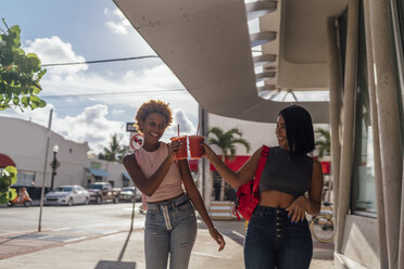 USA, Florida, Miami Beach, two happy female friends having a soft drink in the city - BOYF01161