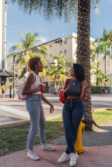 USA, Florida, Miami Beach, two happy female friends having a soft drink in the city - BOYF01170