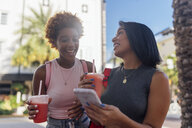 USA, Florida, Miami Beach, two happy female friends with cell phone and soft drink in the city - BOYF01173