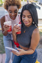 USA, Florida, Miami Beach, two happy female friends with cell phone and soft drink in the city - BOYF01176