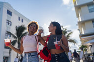 USA, Florida, Miami Beach, two happy female friends having a soft drink in the city - BOYF01185