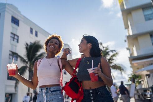USA, Florida, Miami Beach, two happy female friends having a soft drink in the city - BOYF01185