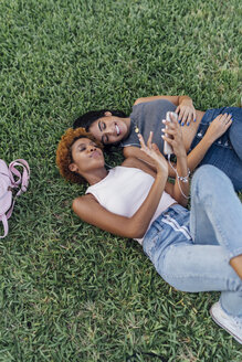 Two female friends relaxing in a park listening to music - BOYF01191