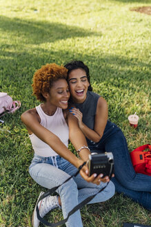 Two happy female friends taking an instant photo in a park - BOYF01200