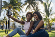 Two happy female friends taking an instant photo in a park - BOYF01203