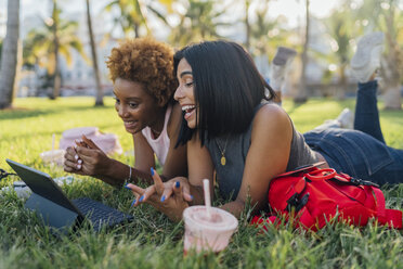 Two happy female friends relaxing in a park using a tablet - BOYF01206