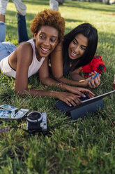 Two happy female friends relaxing in a park using a tablet - BOYF01212