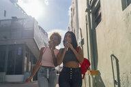 USA, Florida, Miami Beach, two female friends eating ice cream cones in the city - BOYF01218