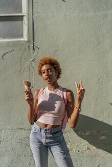 Portrait of young woman with ice cream cone posing at a wall - BOYF01227
