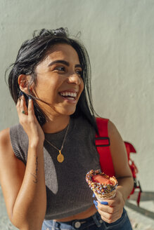 Portrait of happy young woman with ice cream cone outdoors - BOYF01230