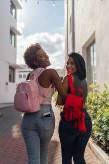 USA, Florida, Miami Beach, rear view of two happy female friends walking in the city - BOYF01233