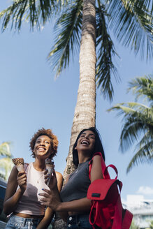 Two happy female friends with ice cream cones at a palm tree - BOYF01236