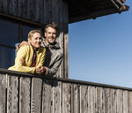 Couple leaning on balcony of a mountain hut, with arms around - UUF15957