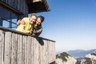 Couple leaning on balcony of a mountain hut, with arms around - UUF15960