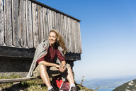 Laughing woman taking a break at a mountain hut - UUF15984