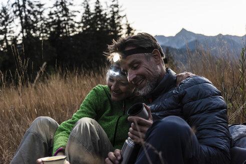 Hiking couple taking a break in the evening, wearing head lamps, drinking tea - UUF16041