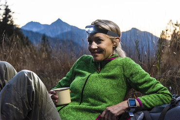 Hiking woman taking a break, drinking tea, wearing head lamp - UUF16044