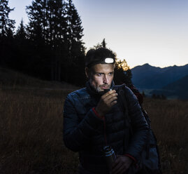 Hiker with head lamp, drinking tea - UUF16047