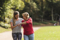 Granddaughter and grandmother having fun, jogging together in the park - UUF16050