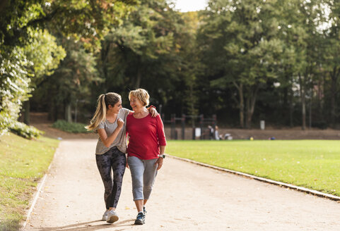 Granddaughter and grandmother having fun, jogging together in the park - UUF16053