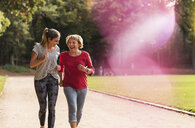 Granddaughter and grandmother having fun, jogging together in the park - UUF16056