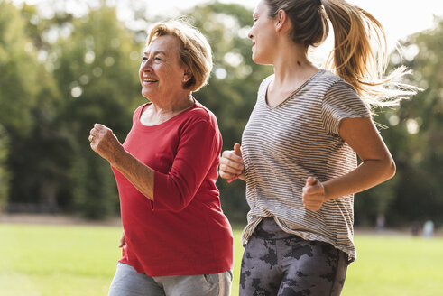 Granddaughter and grandmother having fun, jogging together in the park - UUF16062