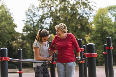 Grandmother and granddaughter training on bars in a park - UUF16065