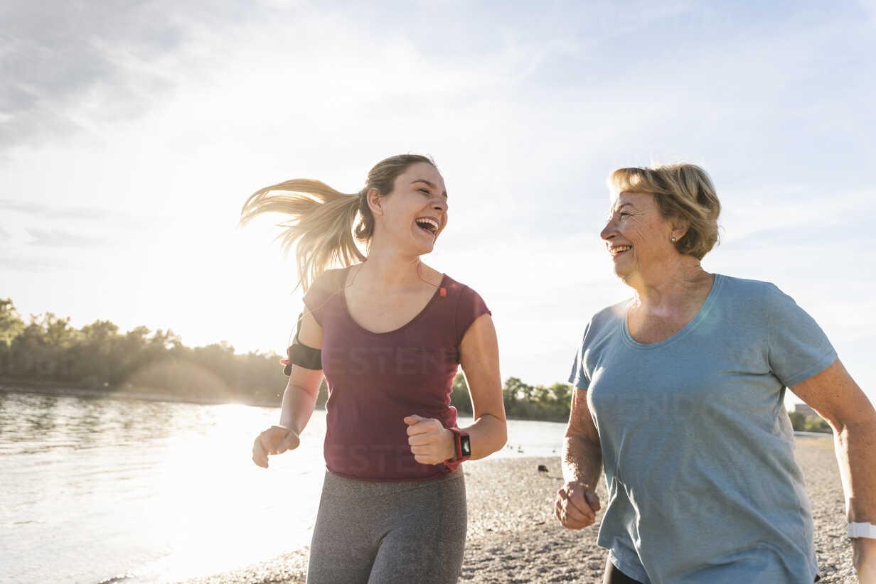 Granddaughter and grandmother having fun, jogging together at the river - UUF16080 - Uwe Umstätter/Westend61