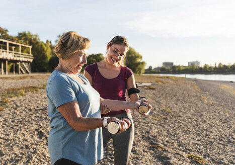 Granddaughter doing dumbbell training with her grandmother at the river - UUF16095