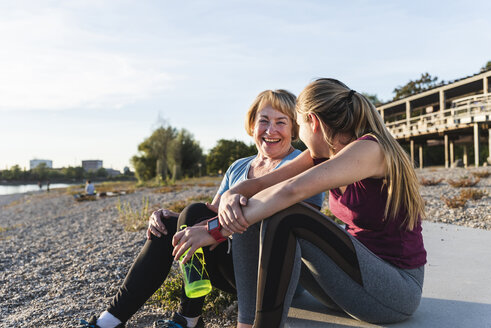 Grandmother and granddaughter taking a break after exercising at the river - UUF16104