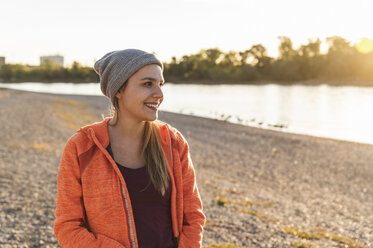 Portrait of a sportive young woman at the river, weraing a beanie hat - UUF16119