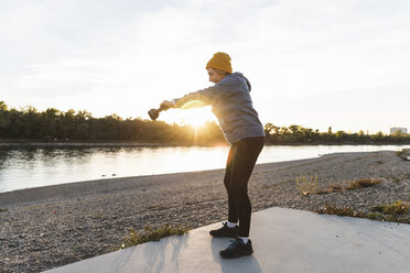 Senior woman exercising with a kettlebell at the river - UUF16122