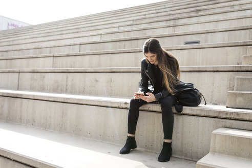 Young woman sitting on stairs using cell phone - VABF01939