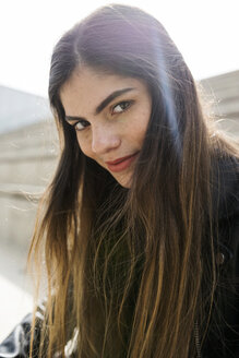 Portrait of confident young woman with long brown hair outdoors - VABF01948