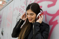 Happy young woman listening to music with headphones at graffiti wall - VABF01960