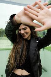 Happy young woman raising her hands - VABF01963