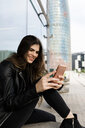 Spain Barcelona, smiling young woman using cell phone in the city - VABF01969
