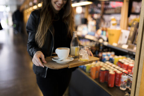 Close-up of woman carrying tray with coffee and soft drink in a self service cafe - VABF01978