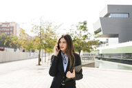 Young businesswoman talking on cell phone in the city - VABF01987