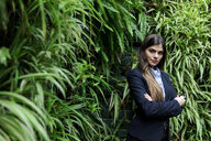 Portrait of confident young businesswoman surrounded by plants - VABF01993