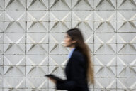 Blurred young businesswoman holding tablet passing concrete wall - VABF02008