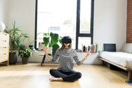 Young woman at home wearing VR glasses doing yoga - VABF02044