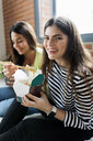 Two happy young women having Asian takeaway food at home - VABF02050